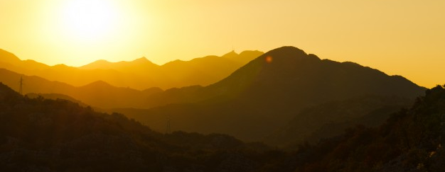Beautiful sillouetteof sunlit mountains, colors of yellow, orange, and brown