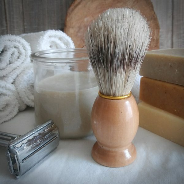 boars hair shave brush light wood handle, glass cup of white soap, old fashioned razor, three natural soaps, wood background