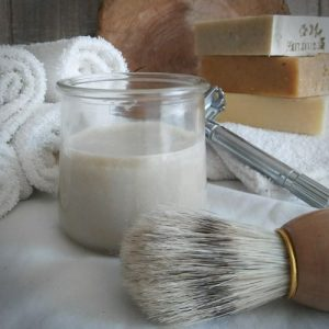 shaving cream for sensitive skin in a repurposed glass cup, boars hair shave brush for lathering